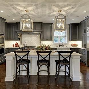 Große Klassische Wohnküche in U-Form mit grauen Schränken, Küchenrückwand in Weiß, Küchengeräten aus Edelstahl, dunklem Holzboden, Kücheninsel, profilierten Schrankfronten, Landhausspüle, Mineralwerkstoff-Arbeitsplatte, braunem Boden, weißer Arbeitsplatte und Rückwand aus Keramikfliesen in Minneapolis