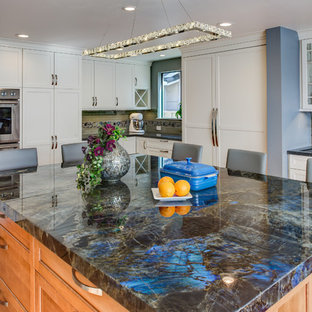 Eat-in kitchen - large transitional u-shaped medium tone wood floor eat-in kitchen idea in San Francisco with an undermount sink, shaker cabinets, white cabinets, granite countertops, gray backsplash, glass tile backsplash, stainless steel appliances and an island