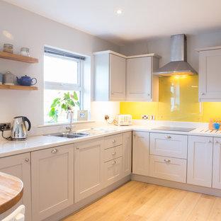 Contemporary kitchen in Dublin with yellow splashback and glass sheet splashback.
