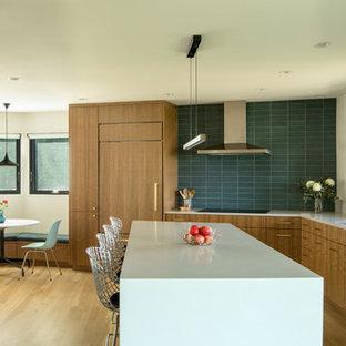 ポートランドの中サイズのミッドセンチュリースタイルのおしゃれなキッチン (フラットパネル扉のキャビネット、中間色木目調キャビネット、グレーのキッチンパネル、シルバーの調理設備、淡色無垢フローリング、茶色い床、グレーのキッチンカウンター) の写真