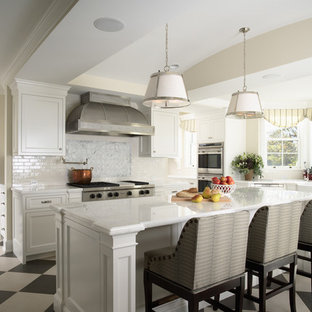 Photo of a large traditional u-shaped separate kitchen in Minneapolis with stainless steel appliances, a farmhouse sink, recessed-panel cabinets, white cabinets, marble benchtops, white splashback, stone tile splashback, with island and multi-coloured floor.
