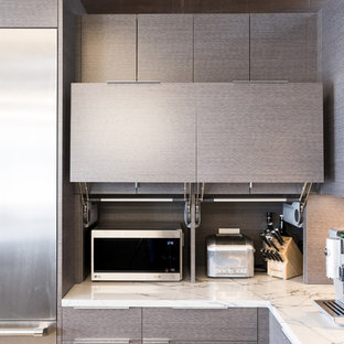 Design ideas for a midcentury kitchen in Louisville with flat-panel cabinets, grey cabinets, marble benchtops, stone slab splashback, stainless steel appliances and white benchtop.