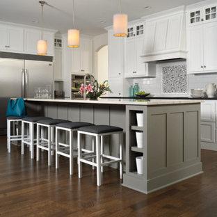 Mittelgroße Moderne Wohnküche in L-Form mit Landhausspüle, Schrankfronten im Shaker-Stil, weißen Schränken, Quarzit-Arbeitsplatte, Küchenrückwand in Weiß, Rückwand aus Metrofliesen, Küchengeräten aus Edelstahl, dunklem Holzboden, Kücheninsel und braunem Boden in Providence