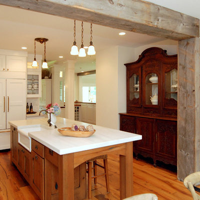 Inspiration for a mid-sized rustic l-shaped medium tone wood floor eat-in kitchen remodel in New York with recessed-panel cabinets, white cabinets, gray backsplash, stainless steel appliances, an island, a farmhouse sink, marble countertops and stone tile backsplash