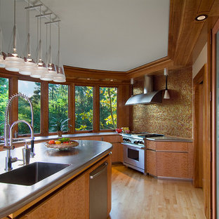 Design ideas for a contemporary kitchen in Cincinnati with stainless steel benchtops, an integrated sink, metallic splashback, mosaic tile splashback, flat-panel cabinets, medium wood cabinets and stainless steel appliances.