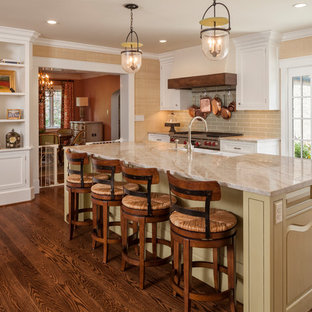 Traditional enclosed kitchen pictures - Inspiration for a timeless medium tone wood floor enclosed kitchen remodel in Cincinnati with a farmhouse sink, shaker cabinets, white cabinets, gray backsplash, subway tile backsplash, stainless steel appliances, an island and granite countertops