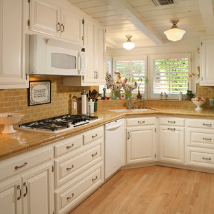 Photo of a traditional separate kitchen in Los Angeles with tile benchtops, white appliances, raised-panel cabinets, white cabinets, brown splashback and subway tile splashback.