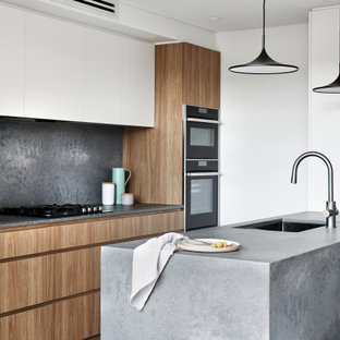 Mid-sized scandinavian single-wall eat-in kitchen in Sydney with an undermount sink, flat-panel cabinets, medium wood cabinets, quartz benchtops, grey splashback, black appliances, dark hardwood floors, with island, brown floor and grey benchtop.