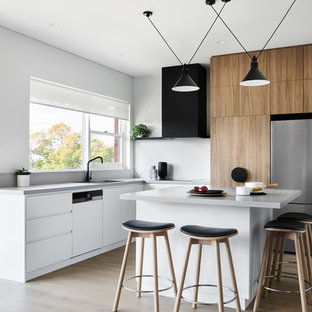 This is an example of a mid-sized contemporary l-shaped kitchen in Sydney with a double-bowl sink, flat-panel cabinets, medium wood cabinets, white splashback, stainless steel appliances, medium hardwood floors, with island, brown floor and grey benchtop.