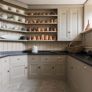 Inspiration for a country u-shaped kitchen pantry in London with a belfast sink, shaker cabinets, beige cabinets, beige splashback, wood splashback, no island and grey floors.