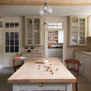 Immagine di una cucina parallela country chiusa con isola, lavello sottopiano, ante in stile shaker, ante beige, top in legno, paraspruzzi beige, paraspruzzi in legno, elettrodomestici colorati e pavimento grigio