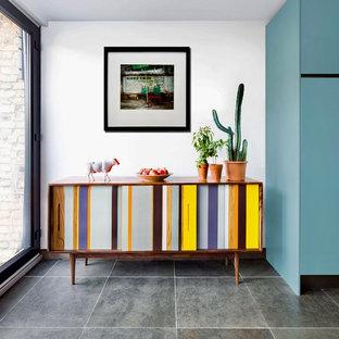 ロンドンの中サイズのコンテンポラリースタイルのおしゃれなアイランドキッチン (フラットパネル扉のキャビネット、ターコイズのキャビネット、セラミックタイルの床、グレーの床) の写真