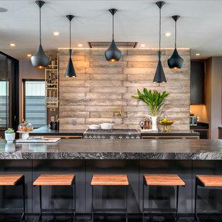 Modelo de cocina en U, contemporánea, grande, abierta, con fregadero bajoencimera, armarios con paneles lisos, puertas de armario grises, encimera de mármol, salpicadero marrón, salpicadero de madera, electrodomésticos de acero inoxidable y una isla
