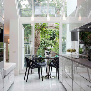 Design ideas for a mid-sized modern galley eat-in kitchen in London with flat-panel cabinets, glass sheet splashback, an undermount sink, white cabinets, quartzite benchtops, black splashback, stainless steel appliances, marble floors and no island.