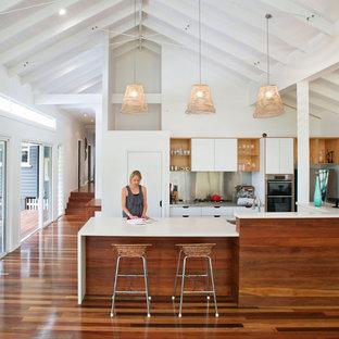 Modern inredning av ett kök, med släta luckor, vita skåp, stänkskydd med metallisk yta och stänkskydd i metallkakel