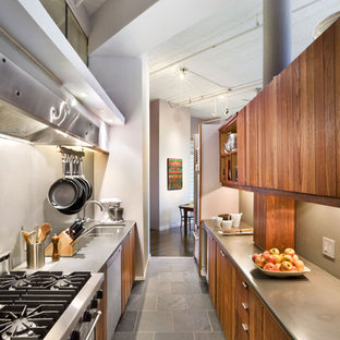 Design ideas for an industrial galley enclosed kitchen in New York with stainless steel appliances, a submerged sink, flat-panel cabinets, medium wood cabinets and slate flooring.