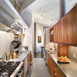 ニューヨークのインダストリアルスタイルのおしゃれなキッチン (シルバーの調理設備、アンダーカウンターシンク、フラットパネル扉のキャビネット、中間色木目調キャビネット、スレートの床) の写真