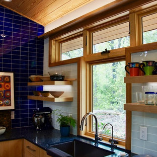 Inspiration for a small contemporary l-shaped open plan kitchen in Raleigh with an undermount sink, flat-panel cabinets, medium wood cabinets, recycled glass benchtops, black splashback, glass tile splashback, stainless steel appliances, concrete floors, no island and grey floor.