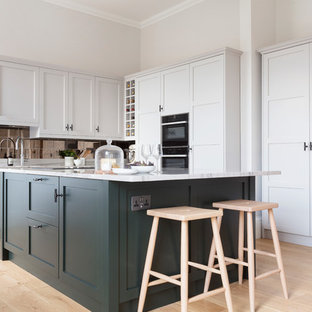 Design ideas for a medium sized classic l-shaped kitchen in Edinburgh with a built-in sink, shaker cabinets, green cabinets, granite worktops, metallic splashback, mirror splashback, black appliances, an island, white worktops, light hardwood flooring and beige floors.