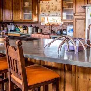 ソルトレイクシティの中くらいのサンタフェスタイルのおしゃれなキッチン (エプロンフロントシンク、レイズドパネル扉のキャビネット、中間色木目調キャビネット、コンクリートカウンター、メタリックのキッチンパネル、メタルタイルのキッチンパネル、シルバーの調理設備、コンクリートの床、赤い床、緑のキッチンカウンター) の写真