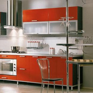 Diseño de cocina comedor moderna, pequeña, con fregadero encastrado, armarios con paneles lisos, puertas de armario naranjas, salpicadero blanco, salpicadero de azulejos de cerámica, electrodomésticos de acero inoxidable y suelo de madera clara