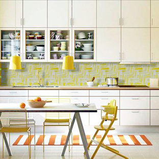 Photo of a mid-sized modern single-wall eat-in kitchen in Gold Coast - Tweed with white cabinets, yellow splashback, a double-bowl sink, glass tile splashback, glass-front cabinets, laminate benchtops, white appliances, porcelain floors, no island, white floor and brown benchtop.