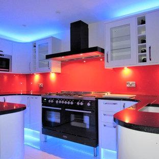 Zweizeilige, Große Moderne Wohnküche mit Waschbecken, weißen Schränken, Granit-Arbeitsplatte, Küchenrückwand in Rot, Glasrückwand, schwarzen Elektrogeräten, Marmorboden und Halbinsel in London
