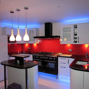 Large modern eat-in kitchen designs - Eat-in kitchen - large modern galley marble floor eat-in kitchen idea in London with a single-bowl sink, white cabinets, granite countertops, red backsplash, glass sheet backsplash, black appliances and a peninsula