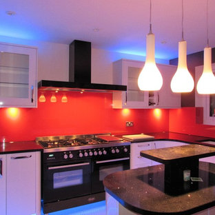 Large modern eat-in kitchen pictures - Large minimalist galley marble floor eat-in kitchen photo in London with a single-bowl sink, white cabinets, granite countertops, red backsplash, glass sheet backsplash, black appliances and a peninsula