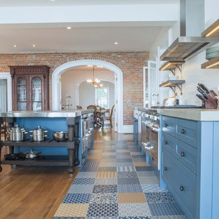 Inspiration for a large traditional single-wall open plan kitchen in Toronto with shaker cabinets, blue cabinets, concrete benchtops, white splashback, stainless steel appliances, ceramic floors, with island, a farmhouse sink, porcelain splashback and multi-coloured floor.
