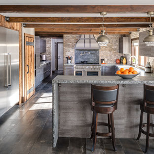 Photo of a large country l-shaped kitchen in New York with a farmhouse sink, grey cabinets, concrete benchtops, brick splashback, stainless steel appliances, porcelain floors, a peninsula and flat-panel cabinets.