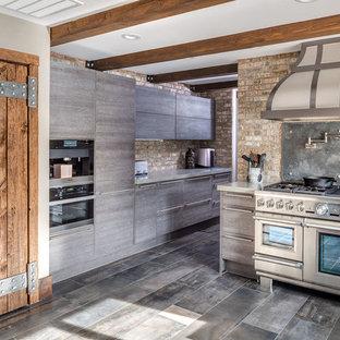 Esempio di una grande cucina a L country con lavello stile country, ante grigie, top in cemento, paraspruzzi in mattoni, elettrodomestici in acciaio inossidabile, pavimento in gres porcellanato e penisola