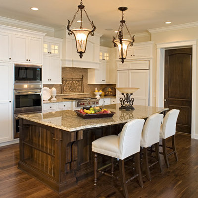 Example of a classic kitchen design in Minneapolis with recessed-panel cabinets, white cabinets, beige backsplash and paneled appliances