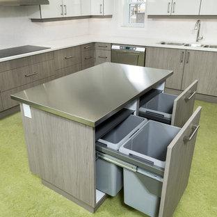 Réalisation d'une cuisine design de taille moyenne avec un placard à porte plane, des portes de placard grises, un plan de travail en quartz modifié, un électroménager en acier inoxydable et un îlot central.
