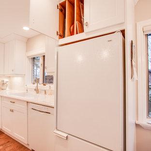 Transitional kitchen remodeling - Example of a transitional kitchen design in Toronto with an undermount sink, recessed-panel cabinets, white cabinets, quartz countertops, white backsplash, ceramic backsplash and white appliances