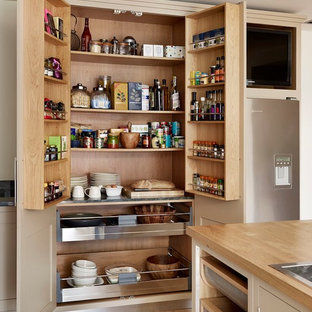 Design ideas for a large contemporary kitchen pantry in London with flat-panel cabinets, beige cabinets and wood benchtops.