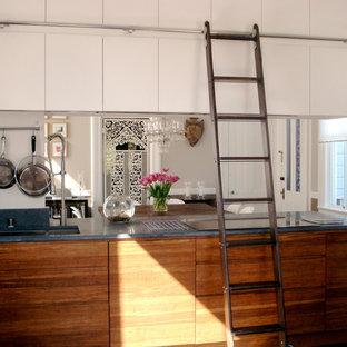 На фото: кухня в стиле фьюжн с обеденным столом, плоскими фасадами, белыми фасадами и синей столешницей с