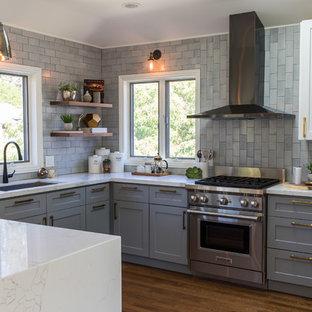 Exemple d'une cuisine chic en U avec un évier encastré, un placard à porte persienne, des portes de placard grises, une crédence grise, un électroménager en acier inoxydable, un sol en bois brun, un sol marron et un plan de travail turquoise.