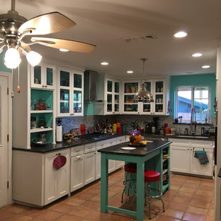 Mid-sized eclectic u-shaped open plan kitchen in Dallas with an undermount sink, glass-front cabinets, white cabinets, granite benchtops, grey splashback, glass tile splashback, stainless steel appliances, terra-cotta floors, with island and beige floor.
