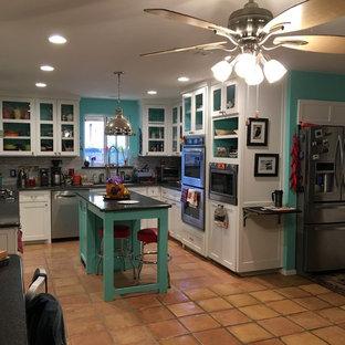 ダラスの中サイズのエクレクティックスタイルのおしゃれなキッチン (アンダーカウンターシンク、ガラス扉のキャビネット、白いキャビネット、御影石カウンター、グレーのキッチンパネル、ガラスタイルのキッチンパネル、シルバーの調理設備、テラコッタタイルの床、ベージュの床) の写真