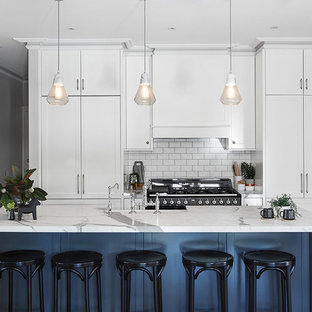 Inspiration for a transitional u-shaped kitchen in Melbourne with shaker cabinets, white cabinets, grey splashback, black appliances, medium hardwood floors, with island, brown floor and white benchtop.