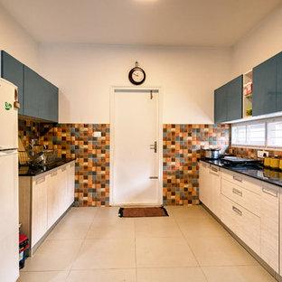 バンガロールのアジアンスタイルのおしゃれなキッチン (フラットパネル扉のキャビネット、淡色木目調キャビネット、マルチカラーのキッチンパネル、白い調理設備、黒い床、黒いキッチンカウンター) の写真