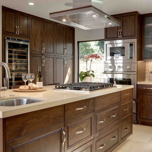 This is an example of a large contemporary l-shaped eat-in kitchen in Los Angeles with raised-panel cabinets, mosaic tile splashback, stainless steel appliances, dark wood cabinets, an undermount sink, with island, quartz benchtops, multi-coloured splashback and limestone floors.