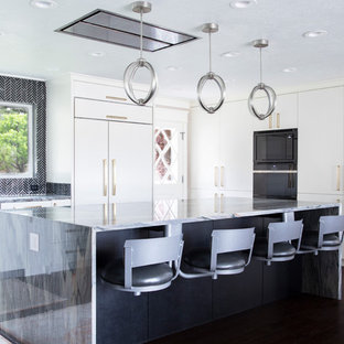 Photo of a mid-sized contemporary kitchen in Salt Lake City with flat-panel cabinets, white cabinets, black splashback, ceramic splashback, dark hardwood floors, with island, brown floor, granite benchtops, panelled appliances and multi-coloured benchtop.