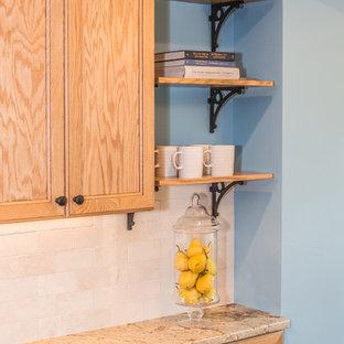 他の地域の中くらいのトラディショナルスタイルのおしゃれなキッチン (エプロンフロントシンク、シェーカースタイル扉のキャビネット、中間色木目調キャビネット、御影石カウンター、ベージュキッチンパネル、セラミックタイルのキッチンパネル、シルバーの調理設備、クッションフロア、茶色い床) の写真