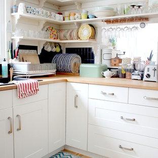 バーリントンのシャビーシック調のおしゃれな独立型キッチン (落し込みパネル扉のキャビネット、白いキャビネット、木材カウンター、黒いキッチンパネル、淡色無垢フローリング、ドロップインシンク) の写真