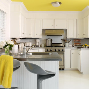 Mid-sized contemporary eat-in kitchen ideas - Inspiration for a mid-sized contemporary u-shaped laminate floor and white floor eat-in kitchen remodel in New York with recessed-panel cabinets, white cabinets, stainless steel appliances, a double-bowl sink, solid surface countertops, white backsplash, a peninsula and gray countertops