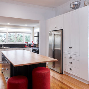 Design ideas for a country l-shaped kitchen in Other with raised-panel cabinets, white cabinets, black splashback, stainless steel appliances, medium hardwood floors, with island, brown floor and black benchtop.