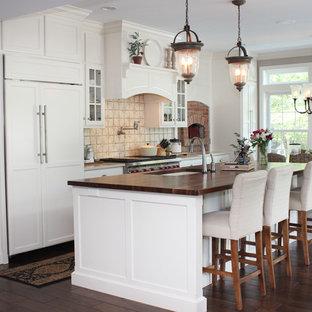 ウィルミントンの広いトラディショナルスタイルのおしゃれなキッチン (アンダーカウンターシンク、シェーカースタイル扉のキャビネット、黄色いキャビネット、珪岩カウンター、ベージュキッチンパネル、テラコッタタイルのキッチンパネル、パネルと同色の調理設備、濃色無垢フローリング) の写真