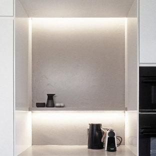 Immagine di una cucina parallela scandinava chiusa e di medie dimensioni con lavello da incasso, ante lisce, ante bianche, top in superficie solida, paraspruzzi grigio, elettrodomestici neri, pavimento in terracotta, penisola, pavimento nero e top grigio